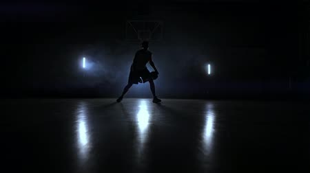 slintání : A man with a basketball on a dark basketball court against the backdrop of a basketball ring in the smoke shows dribbling skills illuminated by three lanterns in backlight