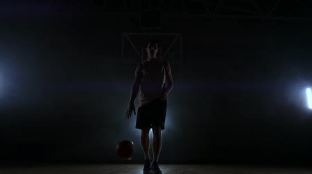 bilenmiş : The basketball player stands on a dark Playground and holds the ball in his hands and looks into the camera in the dark with a backlit in slow motion and around smoke Stok Video