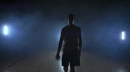 iluminado para trás : Basketball player goes straight to the camera in a dark room with a backlit back in the smoke looking at the camera in slow motion. Steadicam Stock Footage