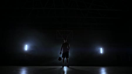 освещенный : The basketball player stands on a dark Playground and holds the ball in his hands and looks into the camera in the dark with a backlit in slow motion and around smoke Стоковые видеозаписи