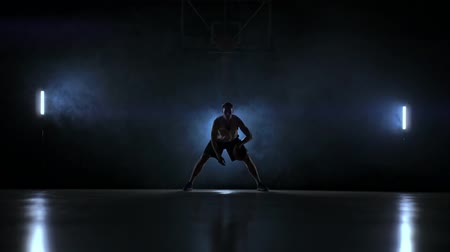 stanovena : A man with a basketball on a dark basketball court against the backdrop of a basketball ring in the smoke shows dribbling skills illuminated by three lanterns in backlight