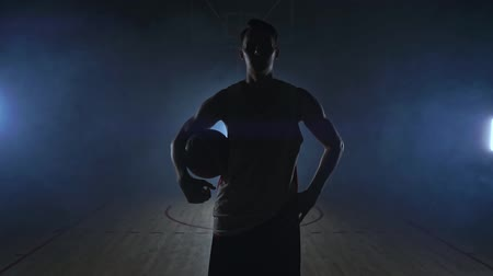 bilenmiş : The basketball player goes to the camera and knocks the ball on the ground then stops and holds the ball looking at the camera