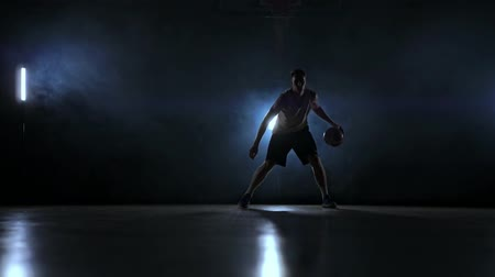 bilenmiş : Skill dribbling basketball player in the dark on the basketball court with backlit back in the smoke. Slow motion streetball