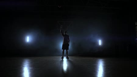 iluminado para trás : Skill dribbling basketball player in the dark on the basketball court with backlit back in the smoke. Slow motion streetball