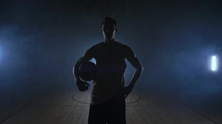 iluminado para trás : The basketball player stands on a dark Playground and holds the ball in his hands and looks into the camera in the dark with a backlit in slow motion and around smoke Stock Footage