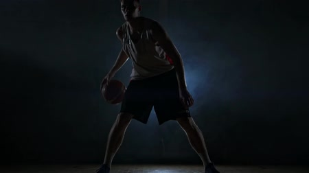 bilenmiş : Dribbling basketball player on the court with the ball in a dark room with a backlight in slow motion in the smoke Stok Video