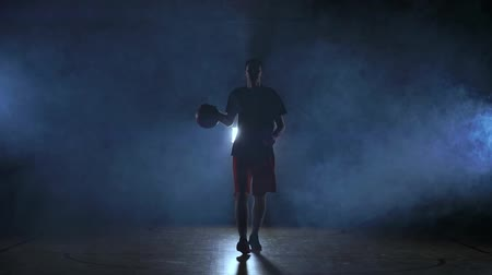 bilenmiş : Basketball player goes straight to the camera in a dark room with a backlit back in the smoke looking at the camera in slow motion. Steadicam Stok Video