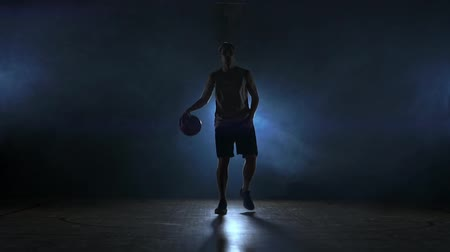 savunma oyuncusu : Basketball player goes straight to the camera in a dark room with a backlit back in the smoke looking at the camera in slow motion. Steadicam Stok Video