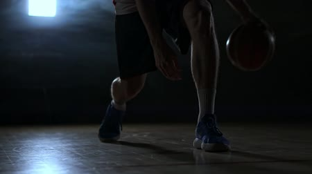 iluminado para trás : Dribbling basketball player close-up in dark room in smoke close-up in slow motion Stock Footage