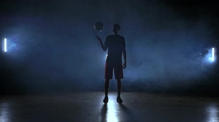 bilenmiş : Basketball player throws and catches the ball in the smoke
