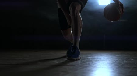 bilenmiş : Dribbling basketball player close-up in dark room in smoke close-up in slow motion Stok Video