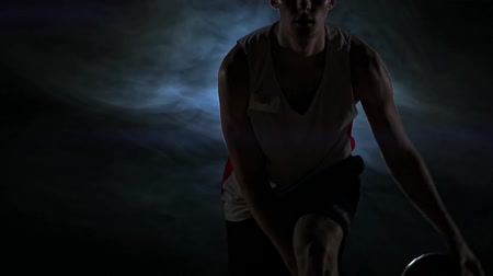 iluminado para trás : Dribbling basketball player on the court with the ball in a dark room with a backlight in slow motion in the smoke Stock Footage