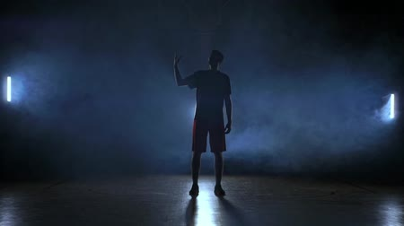 iluminado para trás : Silhouette of a basketball player throwing a ball