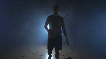 терпение : Basketball player goes straight to the camera in a dark room with a backlit back in the smoke looking at the camera in slow motion. Steadicam Стоковые видеозаписи