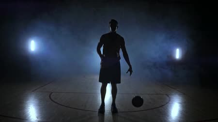 challenger : The basketball player goes to the camera and knocks the ball on the ground then stops and holds the ball looking at the camera