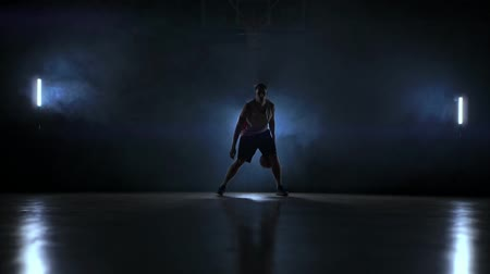 challenger : Dribbling basketball player on the court with the ball in a dark room with a backlight in slow motion in the smoke Stock Footage