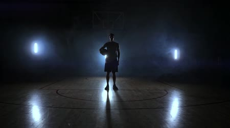 basketball : The basketball player stands on a dark Playground and holds the ball in his hands and looks into the camera in the dark with a backlit in slow motion and around smoke Stock Footage