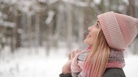 snowy background : Happy beautiful woman in casual style rolling with her hands up while it is snowing on the nice town square in the winter time. Outdoor. Portrait shot Stock Footage