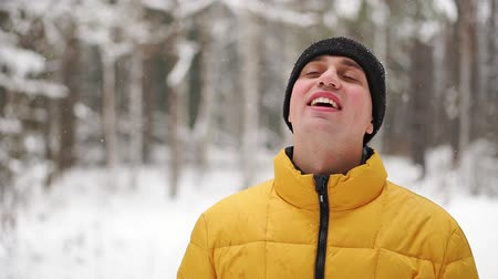 duše : A man in a yellow jacket looks at the snow in the winter in the woods and smiles in slow motion Dostupné videozáznamy