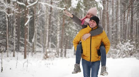 lavoro a maglia : happy loving couple walking in snowy winter forest, spending christmas vacation together. Outdoor seasonal activities. Lifestyle capture. Filmati Stock