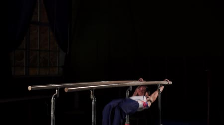 неровной : Male gymnast acrobat performs handstand on parallel bars in a dark room in slow motion