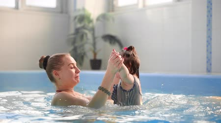 cákanec : Beautiful mother teaching cute baby girl how to swim in a swimming pool. Child having fun in water with mom.
