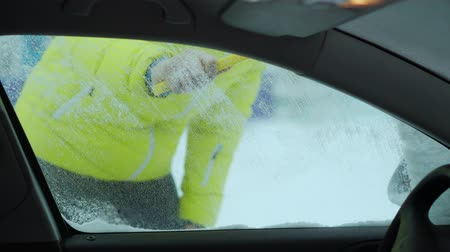 январь : Scraping snow and ice from car windshield. Windshield wipers raised the night before to prevent them getting frozen. Winter driving
