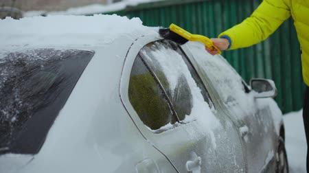emelt : Scraping snow and ice from car windshield. Windshield wipers raised the night before to prevent them getting frozen. Winter driving