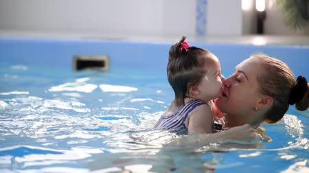fröcskölés : Beautiful mother teaching cute baby girl how to swim in a swimming pool. Child having fun in water with mom.