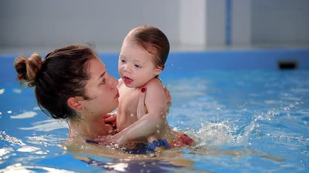 baby blue : Beautiful mother teaching cute baby girl how to swim in a swimming pool. Child having fun in water with mom.