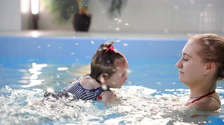 mergulhador : Happy smiling toddler is jumping and diving under the water in the swimming pool. An underwater shot. Slowmotion Stock Footage