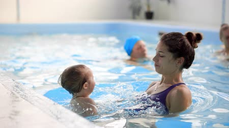 juntar : Mom helps baby to get on the side of the pool during swimming training for babies