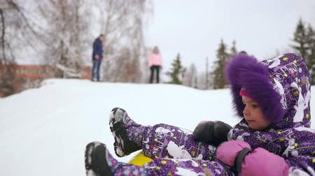toboggan : Happy mom and daughter sledding in winter in snow and playing snowballs. mother and child laugh and rejoice glide on an inflatable tube. Family playing park during Christmas holidays. Slow motion