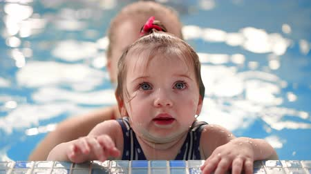 měsíců : Little baby girl while swimming in the pool looking at the camera standing on the side in the water and smiling Dostupné videozáznamy