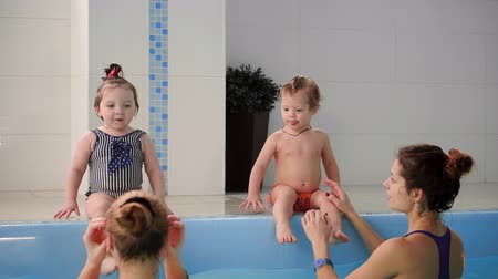 pelenka : Two babies laugh in the pool and jump into the water clapping their hands