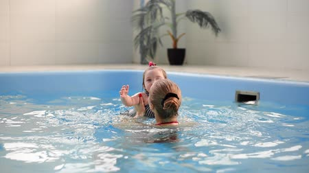 nadador : Cute blonde toddler in protective glasses is diving under the water together with his mother in the swimming pool trying to take out his toy. His mother is teaching him how to swim. An underwater shot.