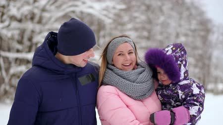 omzunda : Happy family at sunset. Father, mother and two children daughters are having fun and playing on snowy winter walk in nature. The child sits on the shoulders of his father. Frost winter season. Stok Video