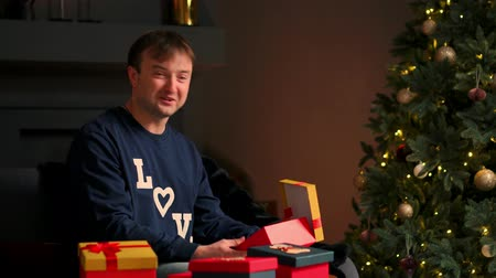 chagrin : Young man with Christmas present in hands opening it sitting on couch