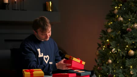 red tape : Young man with Christmas present in hands opening it sitting on couch