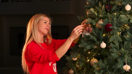 snow globe : Hand of woman decorating Christmas tree with Christmas glow lights.