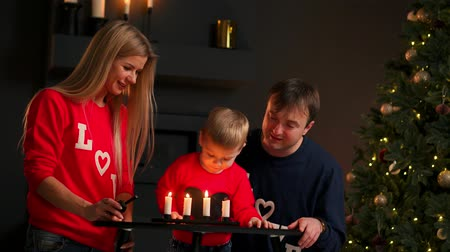 isteyen : Family at Christmas sitting under the tree watching as the child blows out the candles and laughs. Mom and dad laugh and smile