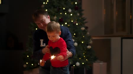 csillagszóró : Young family with sparklers at Christmas time at home.