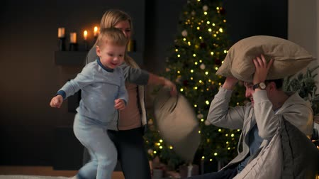 donnine : Happy parents with their son playing sitting on the bed in pajamas at Christmas A pillow fight at Christmas before the new year Filmati Stock