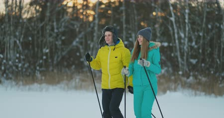 caring : Full length portrait of caring young man helping injured girlfriend during ski walk in winter forest