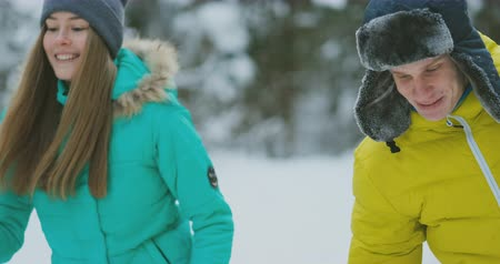 スキーヤー : Loving guy and girl skiing in winter forest in slow motion smiling and looking at each other