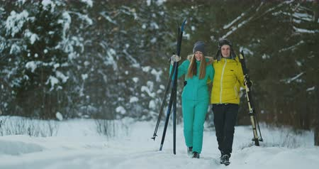 narciarstwo : Full length portrait of active young couple enjoying skiing in snowy winter forest, focus on smiling woman in front, copy space