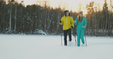 air kiss : A man in a yellow jacket and a girl in a blue jumpsuit skiing in slow motion at sunset