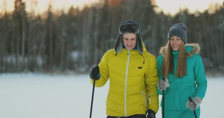 air kiss : Look at each other with loving eyes while skiing in the winter forest. a married couple practices a healthy lifestyle