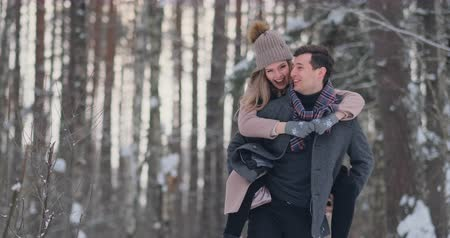 omzunda : Happy Couple is Playing Winter Game Outside Enjoying Sunlight and Warm Winter Weather in the Mountains. Strong Boy is Carrying Girlfriend on His Shoulders and Whirls Her