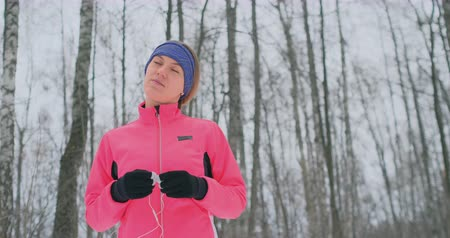 тек : The girl before the morning winter jog inserts headphones in the ears and is preparing to run through the natural Park in slow motion. Listening to music while running. Learn foreign languages